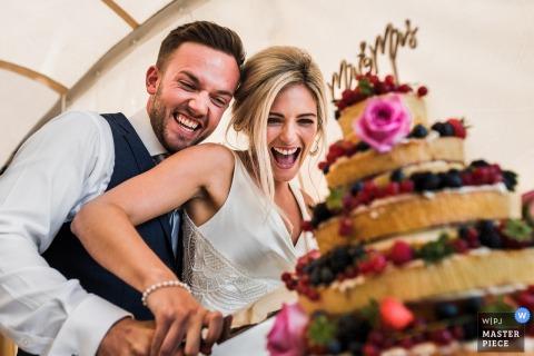 Lachende Braut und Bräutigam, als sie die Hochzeitstorte schneiden Privathaus, Northamptonshire