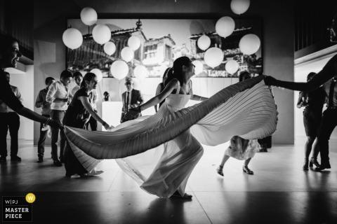 Porto Photojournalisme de mariage | les invités du mariage tiennent la robe de la mariée, elle tourne et danse à la réception
