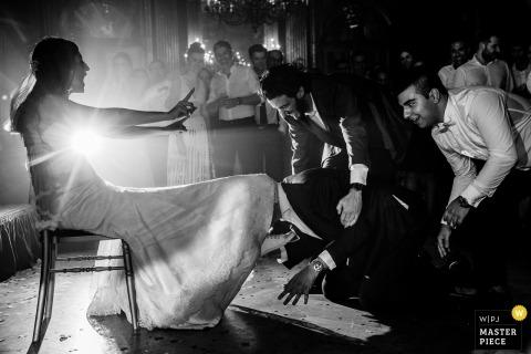 Hyatt Paris wedding photograph of the groom getting the garter from under the brides dress.