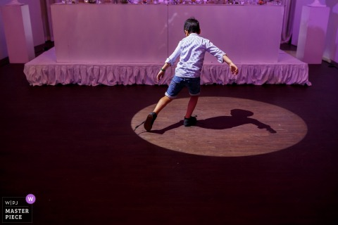 Oldenzaal Wedding Photojournalism | a young boy plays with his shadow from the overhead spotlight
