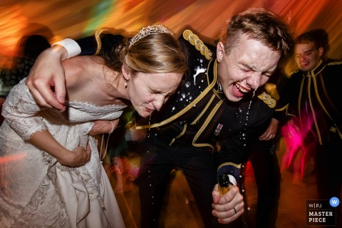Bride and groom spill champagne whilst dancing during their Army wedding in Monmouthshire