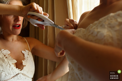 England wedding reportage photo of bridesmaid cutting straps from brides dress