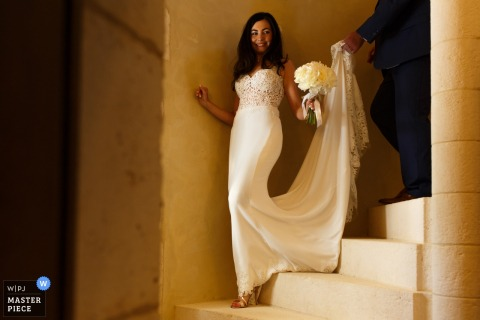 Lancashire Wedding Photojournalism | the bride receives help from her dress as she comes down the stairs in this color photo