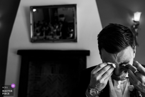 Lancashire Wedding Photojournalism | the groom is wiping both eyes with tissues in this black-and-white photo