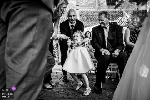 Noord Brabant Wedding Fotojournalistiek | het bloemenmeisje aarzelt om de bruid en bruidegom naar het altaar te naderen