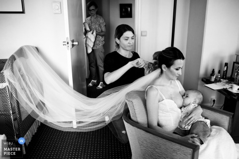 Bucuresti Fotoperiodismo de Boda | Esta novia está amamantando a su bebé mientras su cabello está preparado.