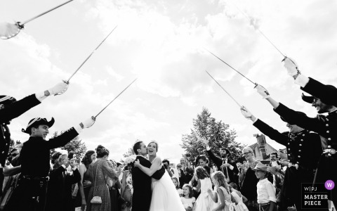 Orléans, France Wedding Photojournalist | a gauntlet of swards greets this bride and groom after the ceremony