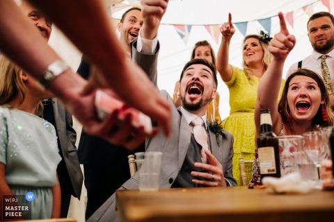 London Wedding Photojournalist | goochelaar vermaakt bruiloftsgasten bij de receptie