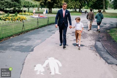 Bruidegom en jonge jongen maken een wandeling in het park