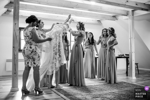 Prague Wedding Photojournalist | the bride is surrounded by bridesmaids and helped into her dress