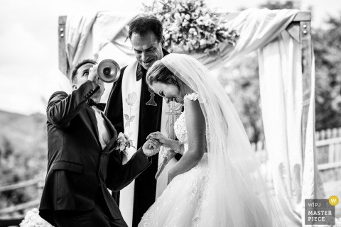 Prague Wedding Photojournalist | the groom drinks from the vessel during the ceremony in this black-and-white photo