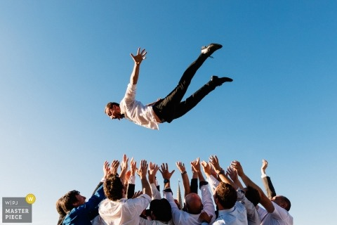 Pyrénées-Atlantiques Wedding Photojournalist | the groom soars like an eagle above the outstretched hands of the groomsmen