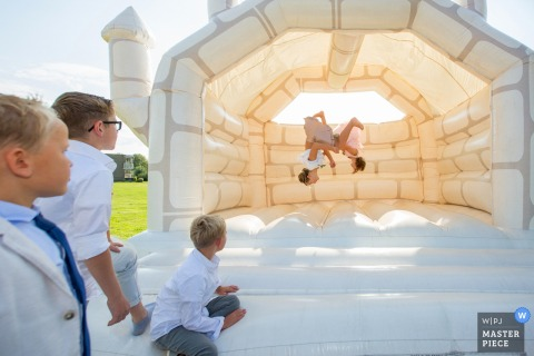 Zuid Holland Wedding Photojournalist | children wait their turn to do flips in the inflatable bouncy house castle