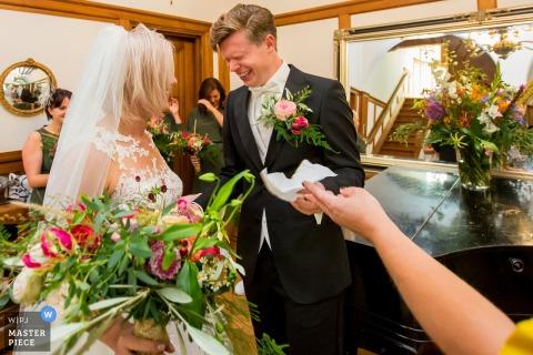 Zuid Holland Photojournaliste de mariage | le marié est envahi par les émotions et se voit offrir un mouchoir en papier lors de la cérémonie de mariage à l'intérieur