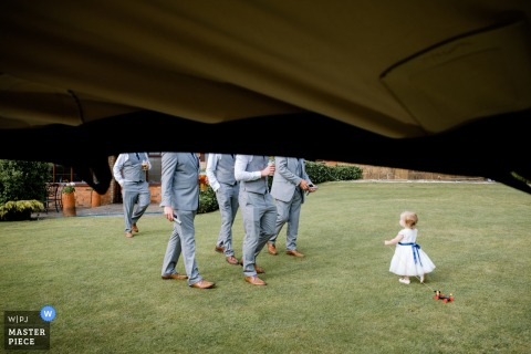 Napton Windmill Wedding Photo of a toddler baby girl on the grass with the groomsmen