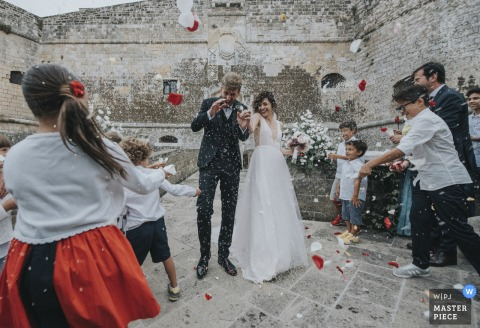 The guests throw rice on the bride and groom | Otranto Castle, Puglia