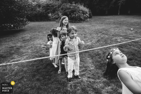 Rouen Wedding Photojournalist | Young children at the wedding reception lineup for limbo games