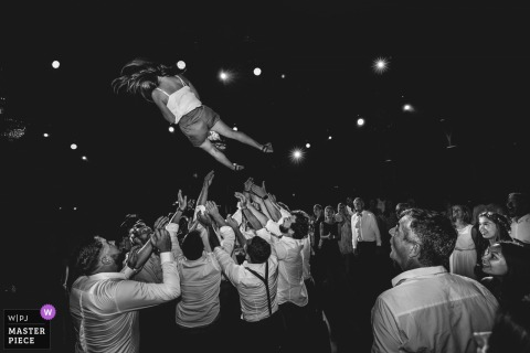 Bruxelles Wedding Photojournalist |  a Young woman is tossed up high into the air by men at the wedding reception