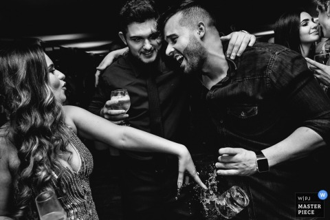 Minas Gerais Wedding Photojournalist | the man has his drink knocked out of his hand on the dance floor