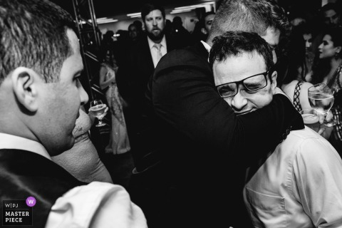 Minas Gerais Wedding Photojournalist | man gets hugged and his glasses smashed into his face