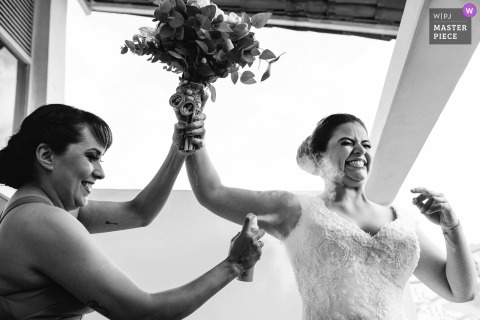 Ouro Preto Wedding Photojournalist | the bride holds her bouquet overhead as the maid of honor sprays deodorant under her arm