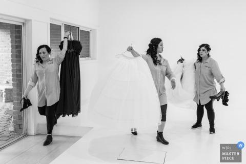 Brautjungfern arbeiten schnell, um die Kleider zu bewegen Blackburn Elizabethan Lodge, Melbourne, Victoria, Australien.
