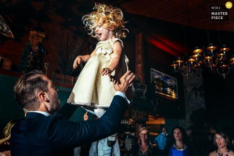 Alberta Boda Fotoperiodista | Una joven con un bonito vestido es lanzada al aire en la recepción de la boda.