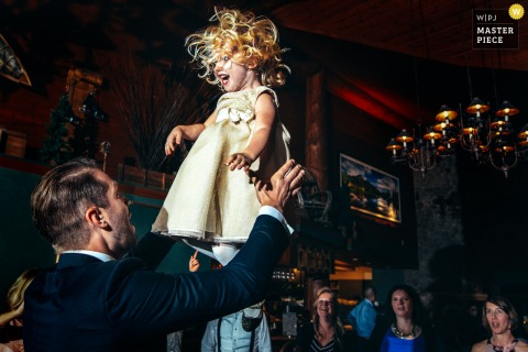 Alberta Wedding Photojournalist | a young girl in a pretty dress is thrown into the air at the wedding reception