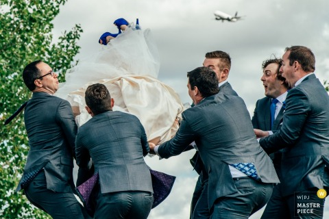 Alberta Wedding Photojournalist | the bride takes flight like a commercial airline with the help from the groomsmen
