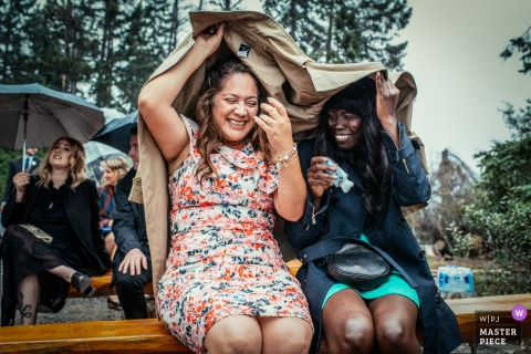 Alberta Wedding Photojournalist | two ladies Cover their heads with a coat as they sit outdoors in the pouring rain during the ceremony