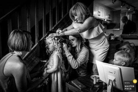Alberta Hochzeitsfotojournalist | Das junge Blumenmädchen ist mit Blumen im lockigen Haar auf die Zeremonie vorbereitet