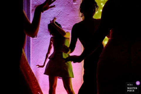 Lisbon Wedding Photojournalist | silhouetted wedding guests dance with pink lights at the reception