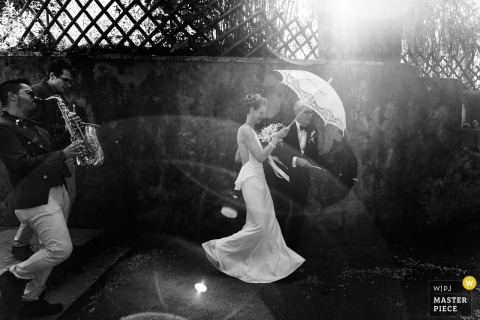 Lisbon Wedding Photojournalist | the bride with a white umbrella under the sun in a black and white image with the saxophone