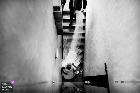 Lisbon Wedding Photojournalist | the groom follows the bride down the stairs while carrying her long veil