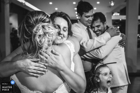Rio de Janeiro Wedding Photojournalist | the bride and groom hug best friends in this black-and-white photo