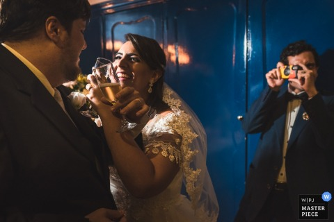 Rio de Janeiro Wedding Photojournalist | the bride and groom toast as a guest snapps a photo using disposable camera