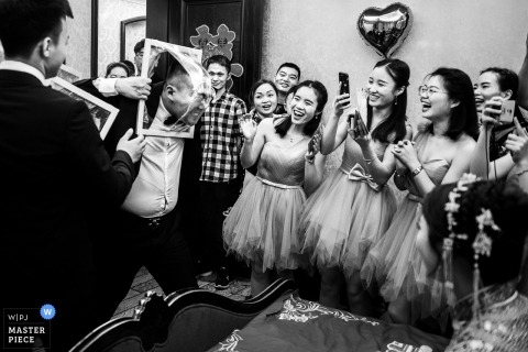 Liaoning Wedding Photojournalist | Chinese door games of groomsmen smashing faces through plastic