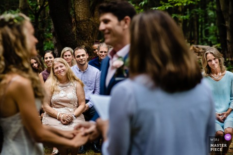 Monkton, VT Wedding Photojournalist | the bride and groom hold hands as they exchange their vows during an outdoor ceremony in the Woods