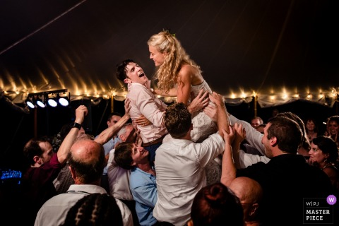 Monkton, VT Wedding Photojournalist | the bride is lifted high above the wedding guests by reception dance floor