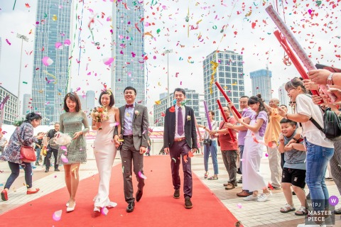 Liaoning Wedding Photojournalist | red carpet and red confetti shot from red cannons as the bride and groom are escorted from the ceremony