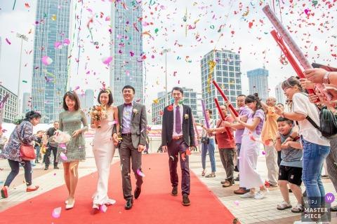 Liaoning Hochzeitsfotojournalist | roter Teppich und rotes Konfetti, die aus roten Kanonen geschossen wurden, als Braut und Bräutigam von der Zeremonie begleitet werden