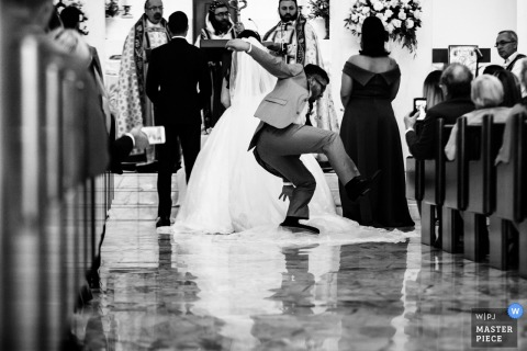 Ontario Wedding Photojournalist | a man falls during the wedding ceremony as he trips on the brides long veil train
