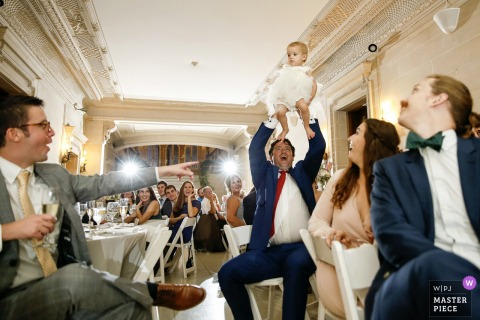 A father raises his baby daughter up as she is mentioned in a speech. | Armour House, Lake Forest, IL