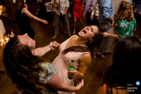 Seattle, WA Wedding Photojournalist | bridesmaids dancing at the reception holding a beer bottle