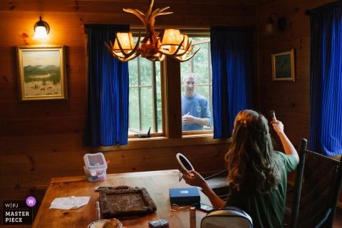 當他們為婚禮做準備時,一位女僕通過窗戶向她的父親說話。 在紐約的婚禮上與爸爸交談。