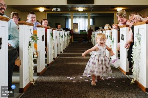 A little flower girl joyfully dashes down the aisle spilling her petals. | Happy Flower Girl