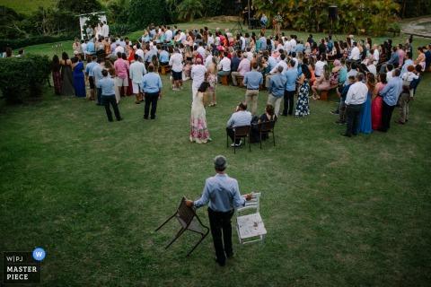 Praia do Rosa - Santa Catarina - Photojournaliste de mariage au Brésil | un homme porte des chaises supplémentaires à la cérémonie de mariage en plein air sur la pelouse