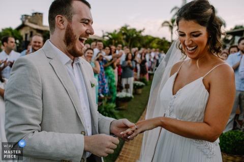 Praia do Rosa - Santa Catarina - Brésil l Mariage Photo du marié sur le point de placer la bague au doigt des mariées dans cette cérémonie de mariage en plein air image