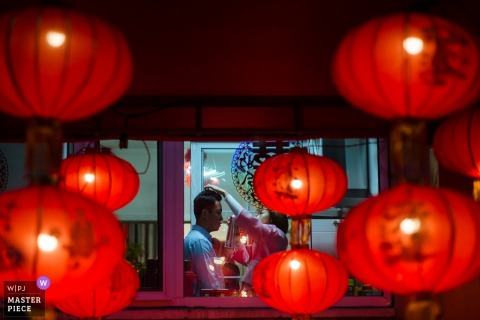 Shanxi Wedding Photojournalist | red lanterns frame this groom getting his hair fixed
