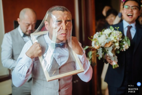 Shanxi Wedding Photojournalist | a man smashes his face through clear plastic during the heat crashing game party